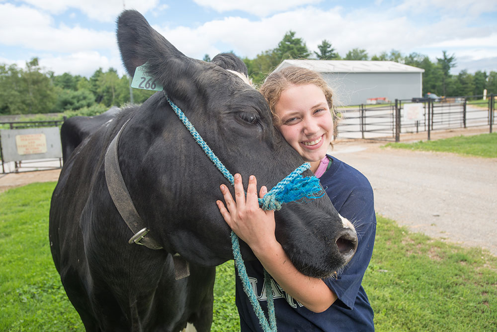 UMaine student hugging a cow