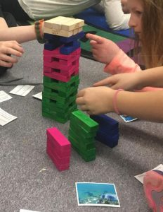 youth play color-coded Jenga game