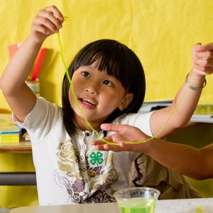 4-Her holding up a string during a science experiment