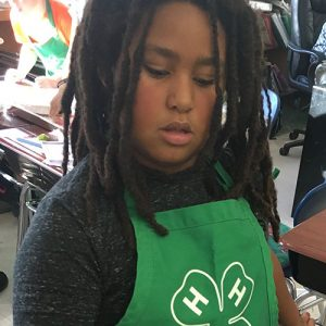 4-Her wearing an apron with the 4-H emblem on it