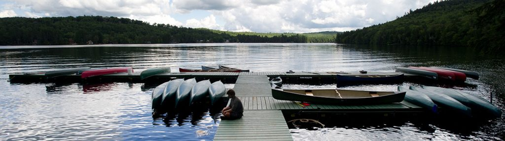 Canoes tied to the dock in Bryant Pond