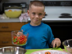 boy prepping berries in a measuring cup for a demonstration