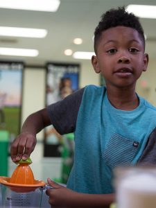 boy using a juicer with lime for a demonstration