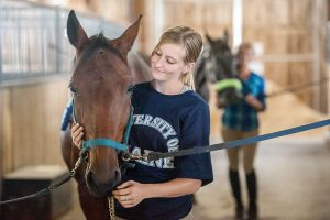 UMaine youth with her horse in a horse barn