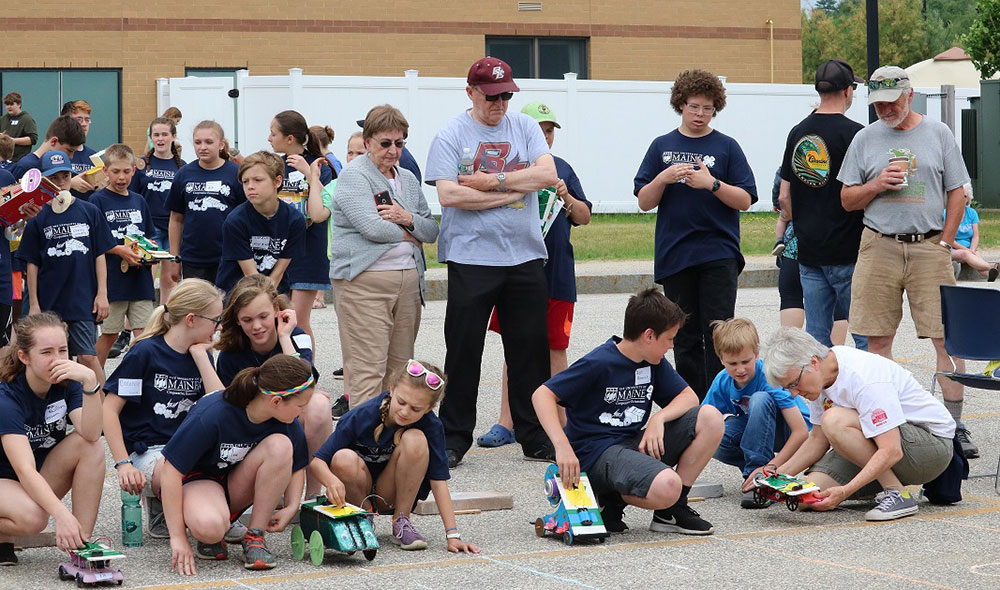 group of youth with solar cars on the starting line with race supporters behind