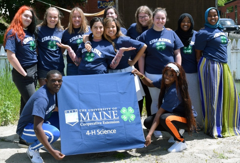 4-H Interns with a 4-H Science banner
