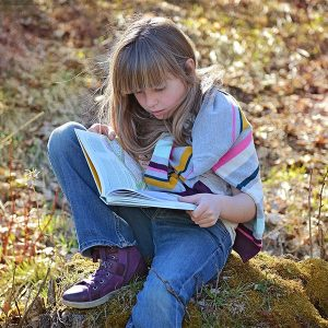 young girl reading a book outside on a lawn