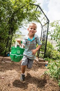 young boy in a garden with a 4-H bag