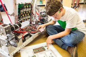 middle school boy working on robotics