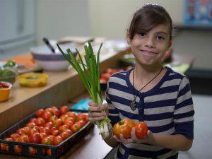 middle school girl holding vegetables