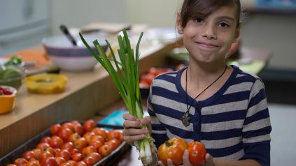 middle school girl holding vegetables