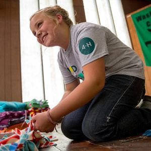 young 4-H girl making a blanket