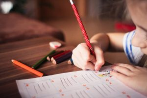 a young girl using crayons and colored pencils on a worksheet