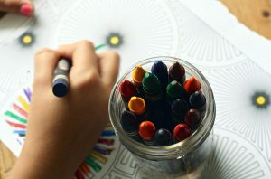 a young child's hand using crayons from a glass jar to color on a coloring sheet