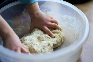 a young child's hands in a bowl, kneading bread dough