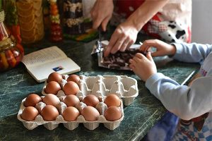 a parent and young child at a kitchen counter using eggs in a recipe