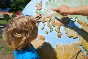 young boy looking at a globe that is located outside in a park