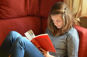 a teen girl sitting on a couch reading a book