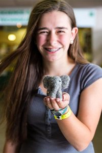 a teen girl with a crafted felt elephant toy