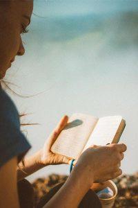 a teen girl reading a journal book