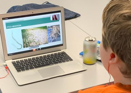young teen boy watching a virtual science cafe session