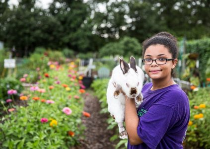 a girl with a rabbit standing in front of a garden