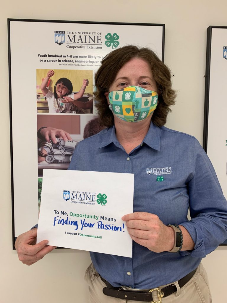 """UMaine Extension Dean Dr. Hannah Carter holding her Opportunity for All sign stating """"To Me, Opportunity Means Finding Your Passion!"""""""