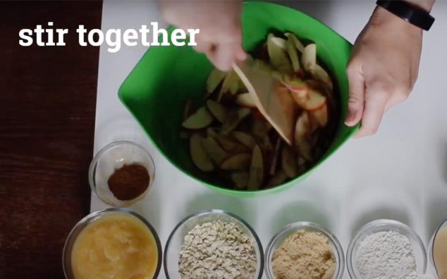 screenshot graphic from a Mainely Dish recipe video, hands stirring apple slices in a bowl