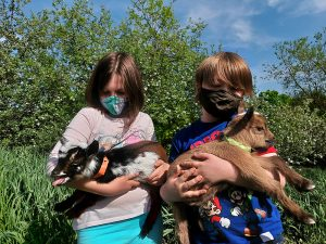 Two Youth holding goat kids.
