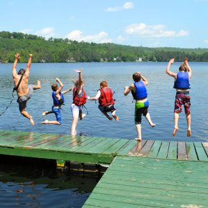 Campers jump off the dock into the lake at the 4-H Camp and Learning Center at Bryant Pond
