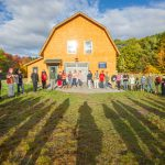 Circle of students in front of a barn,