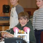 4-H youth smiling with a robot.