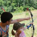 Girl being taught archery at camp.