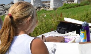 youth drawing a picture outdoors