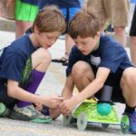two youth with solar-powered race car
