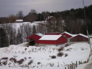 Red barn on hillside in winter