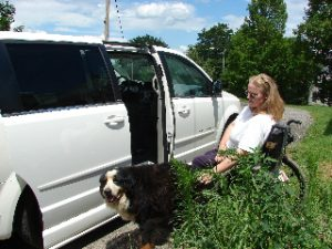 woman in wheelchair and dog getting into van