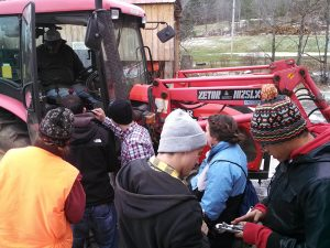 people looking into tractor cab talking with farmer