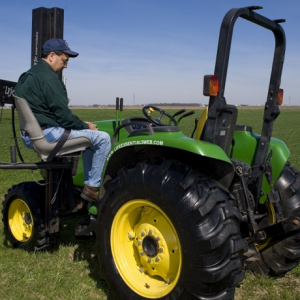 farmer using an assistive device to get onto his tractor