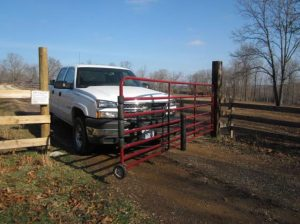 wheeled gate being opened by a pickup truck