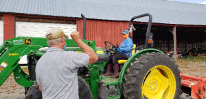 man giving hand signal to woman on tractor