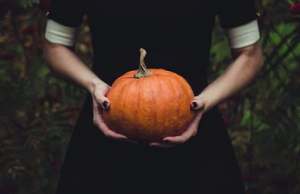 person holding a pumpkin with 2 hands