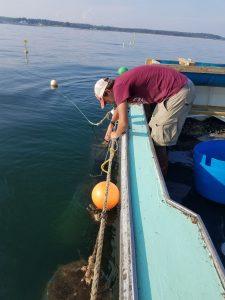 Man bending over boat pulling line