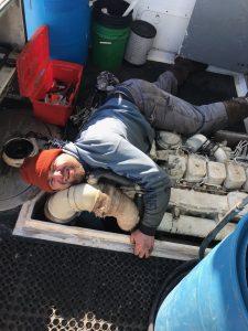 fisherman on boat floor reaching below piping