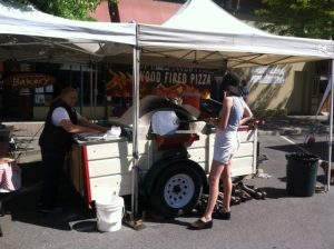 woman standing in front of pizza vendor