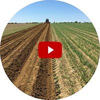 picture of tractor plowing field overlayed with a video play button