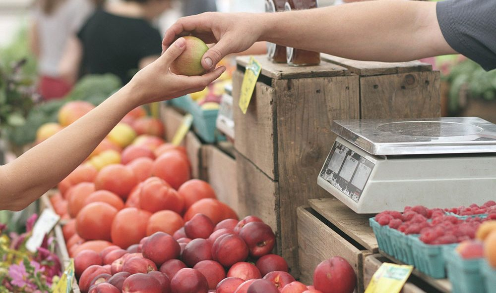 customer buying an apple at a farmers' market