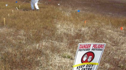 Spraying chemical material with a 4-nozzel boom sprayer with a pesticide warning sign in the fore-ground