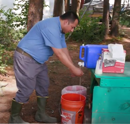Robson demonstrating hand washing in the field