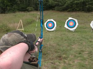 camper shooting archery at target